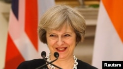 FILE - Britain's Prime Minister Theresa May smiles as her Indian counterpart Narendra Modi (unseen) reads a joint statement at Hyderabad House in New Delhi, India, Nov. 7, 2016.