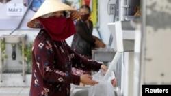 Một phụ nữ nhận gạo từ máy ATM ở TP. Hồ Chí Minh, ngày 11/04/2020.