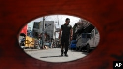 A policeman patrols inside a village that was placed under lockdown as the government implements stricter measures to prevent the spread of the coronavirus in Manila, Philippines on Monday, March 22, 2021.