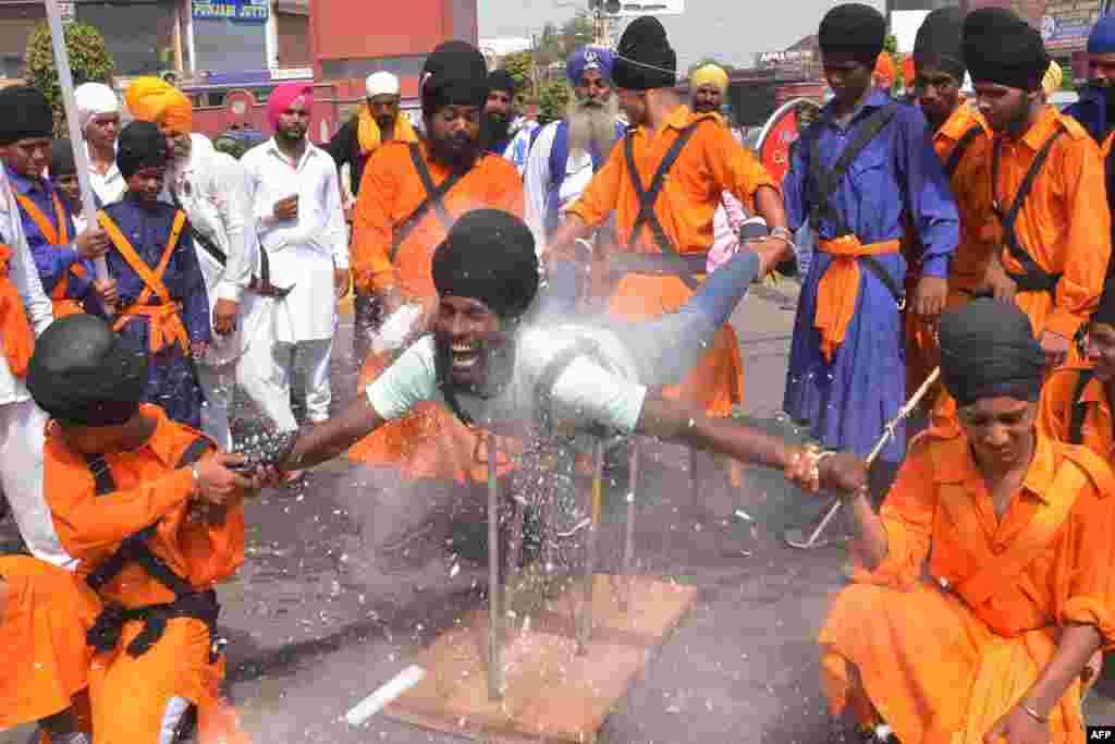 An Nihang Ấn Độ, một chiến binh tôn giáo người Sikh, biểu diễn kỹ năng võ thuật được gọi là 'Gatka' trong một cuộc diễu hành kỷ niệm sinh nhật lần thứ 354 của chiến binh Sikh Shaheed Baba Jiwan Singh tại Đền Vàng ở Amritsar.