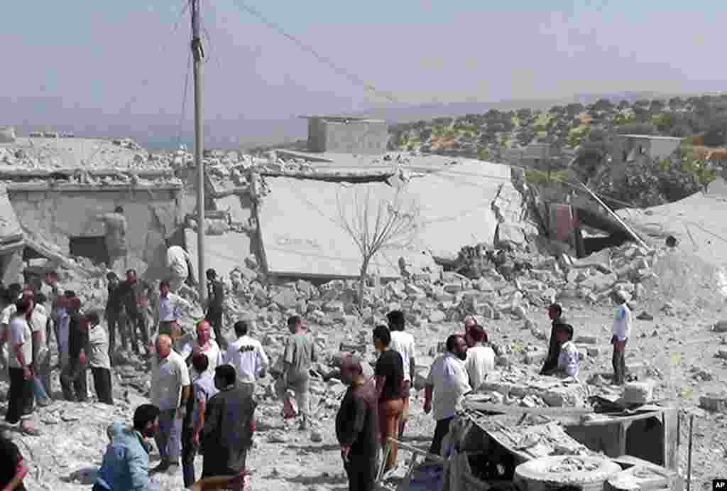 In this citizen journalism image provided by Edlib News Network, ENN, Syrians search under rubble to rescue people from houses that were destroyed by a Syrian government warplane in Idlib province, August 30, 2013.