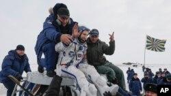 La tripulación aterrizó en una cápsula rusa Soyuz un minuto antes de lo previsto en las estepas cubiertas de nieve de Kazajistán.