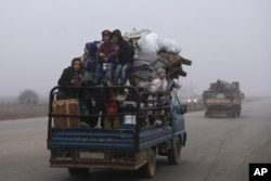 FILE - Civilians ride in a truck as they flee Maaret al-Numan, Syria, ahead of a government offensive, Dec. 23, 2019. The M5 strategic highway is vital for Syria's economy as well as for moving troops.