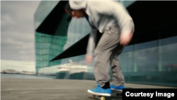 A skateboarder rolls past what is apparently Reykjavik's Harpa concert hall in a screen grab from a promotional video for the U.S. state of Rhode Island. (Rhode Island Commerce Corporation)(