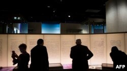 Visitors look at an exhibit about the Dead Sea Scrolls during a media preview of the Museum of the Bible in Washington, D.C., Nov. 14, 2017.