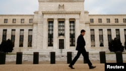FILE - A man walks past the Federal Reserve building in Washington, D.C., Dec. 16, 2015.