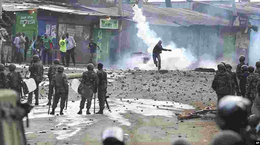 A supporter of opposition leader Raila Odinga throws a canister of tear gas towards riot police during running battles with police in Kibera Slums in Nairobi, Kenya.