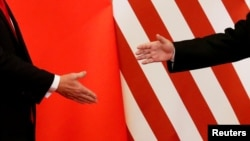 FILE - U.S. President Donald Trump and China's President Xi Jinping shake hands after making joint statements at the Great Hall of the People in Beijing, Nov. 9, 2017.