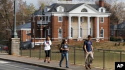 FILE - In this Monday, Nov. 24, 2014, file photo, University of Virginia students walk to campus past the Phi Kappa Psi fraternity house at the University of Virginia in Charlottesville, Va. Rolling Stone retracted a story of sexual attack at the fraternity. (AP Photo/Steve Helber, File)