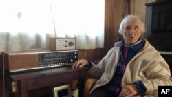 In this photo taken on Sunday, Jan. 8, 2017, 98-year-old Judith Haaland sits next to her decades-old radio set in Stavanger, Norway.