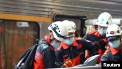 Waokoaji wakiuhamisha mwili katika kituo cha treni cha Xincheng baada ya mabehewa kuacha njia ya treni kwenye handaki lililoko kaskazini ya Hualien,Taiwan, Aprili 2, 2021. REUTERS/Annabelle Chih