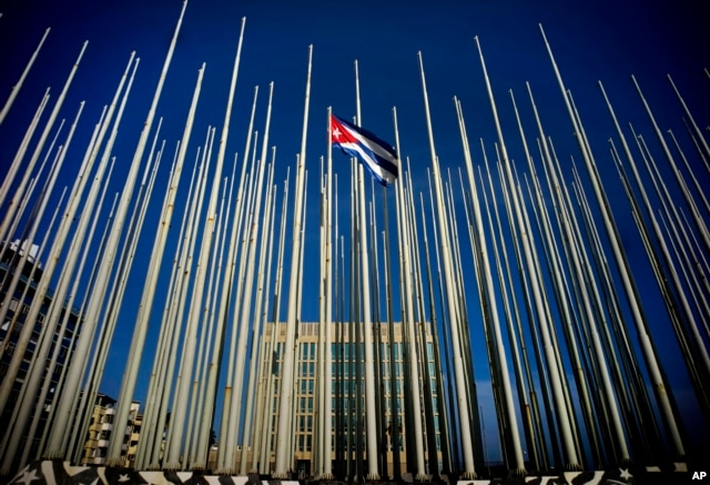 A Cuban flag flies among empty flag polls near the U.S. Interests Section building, behind, in Havana, Sunday, July 19, 2015.