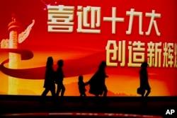 北京居民走過迎接中共十九大召開的大型電子屏幕(2017年10月15日)