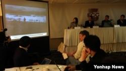 북한 주민들의 탈북과 남한 정착을 지원하는 갈렙선교회의 김성은 목사가 지난 2013년 겨울 북한 접경지역에서 찍은 영상을 공개하고 있다. 기름, 성경책 등을 전달받은 북한 주민 2명이 북-중 국경을 건너가는 모습. (자료사진)