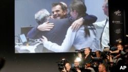 Scientists celebrate at the European Space Agency after the first unmanned spacecraft Philae landed on a comet called 67P/Churyumov-Gerasimenko on Nov. 12, 2014. (AP Photo/Michael Probst)