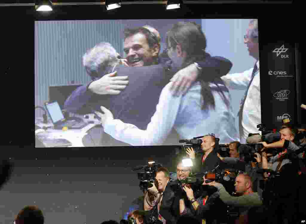 Celebrating scientists in the main control room appear on a video screen at the European Space Agency after the first unmanned spacecraft Philae landed on a comet called 67P/Churyumov-Gerasimenko, in Darmstadt, Germany, Nov. 12, 2014.