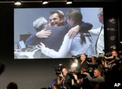 FILE - Scientists celebrating in the main control room appear on a video screen at the European Space Agency after the first unmanned spacecraft Philae landed on a comet called 67P/Churyumov-Gerasimenko, in Darmstadt, Germany, Nov. 12, 2014.
