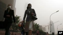 Para pekerja mengenakan masker berjalan di jalanan di Beijing yang dilanda polusi udara dan badai pasir, 4 Mei 2017.