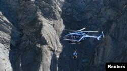 Helikopter penyelamat Perancis mencari puing-puing pesawat Airbus A320 di lokasi jatuhnya, dekat Seyne-les-Alpes, Pegunungan Alpen (27/3). (Reuters/Gonzalo Fuentes)