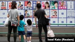 Une famille regarde les affiches des candidats devant un bureau de vote à Tokyo, au Japon, le 5 juillet 2020