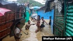 Rohingya refugee children play in flood waters at the Rohingya refugee camp in Kutupalong, Bangladesh, Wednesday, July 28, 2021. (AP Photo/ Shafiqur Rahman)