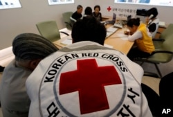 South Koreans who were separated from their families during the Korean War, talk with Red Cross members as they check application forms to reunite with their family members living in North Korea, at the Korea Red Cross headquarters in Seoul, South Korea,