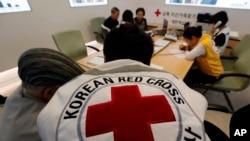在朝鲜战争中分离的韩国庭家成员与红十字会成员交谈,并提交申请与居住在朝鲜的家人团聚