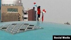 این دختر معترض به حجاب اجباری در حالی که شالی قرمز و بادکنک هایی به رنگ قرمز و سفید در دست داشت، بالای نماد گنبدی شکل میدان انقلاب تهران رفت.