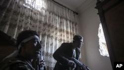 Sirijski pobunjenici osmatraju pokrete vladinih trupa u četvrti Karmal Džabi, u Alepu