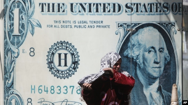 FILE - An Egyptian vendor adjusts her veil in front of a giant poster of a US dollar outside an exchange office in Cairo, Egypt, March 28, 2011.