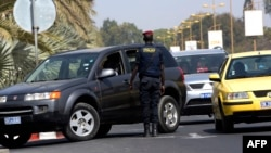 A Senegalese police officer conducts a vehicle inspection at the entrance of a Dakar hotel, Jan. 22, 2016. Security measures have been reinforced close to public buildings, following jihadist attacks in Bamako and Ouagadougou.
