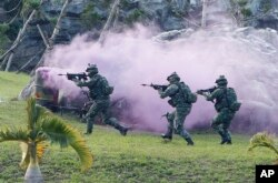 FILE - Soldiers from Taiwan's special forces move past colored smoke during a helicopter landing training and all-out defense demonstration in Taipei, Taiwan, Dec. 14, 2017.