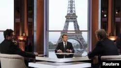 លោកប្រធានាធិបតីបារាំង Emmanuel Macron (រូបកណ្តាល) ផ្តល់បទសម្ភាសន៍ជាមួយនឹងទូរទស្សន៍ BFM កាលពីថ្ងៃទី១៥ ខែមេសា ឆ្នាំ២០១៨។