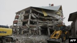 Nhân viên cứu hỏa và binh sĩ tìm kiếm những người sống sót trong đống đổ nát ở Ercis, Van, Thổ Nhĩ Kỳ, 29/10/2011