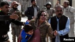 Um polícia ajuda uma família a abandonar a Igreja Metodista em Quetta, Paquistão onde decorreu um ataque. Dez. 17, 2017.