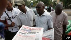 People read newspapers with election headlines on the street in Abuja, Nigeria Monday, March 30, 2015. Nigerians are waiting for results of the tightest and most bitterly contested presidential election in the nation's turbulent history. (AP Photo/Sunday Alamba)