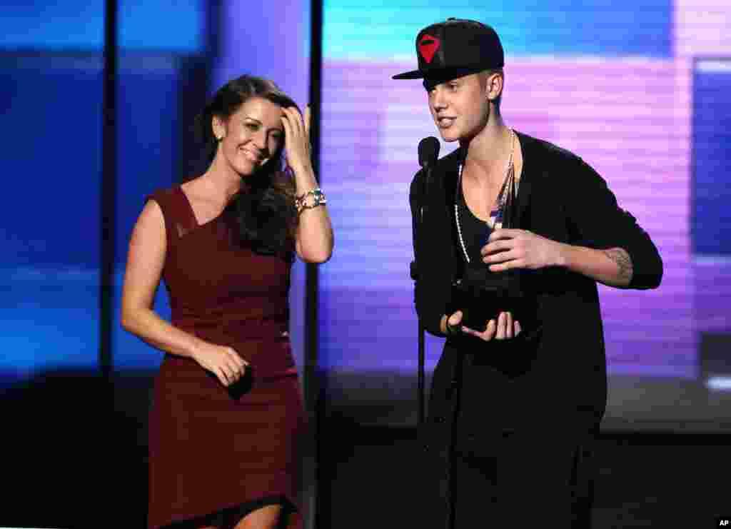 Justin Bieber acepta el premio de Artista del Año ante la mirada de su madre Pattie Malette durante la celebración del 40 aniversario del American Musica Awards 2012.
