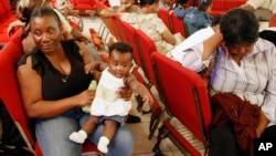 FILE - Haitian national Carole Manigat, left, holds her daughter Hadassa Carole Albert as she waits for her turn to fill out temporary protective status papers at Notre Dame d'Haiti Catholic Church in the Little Haiti neighborhood in Miami, Jan. 21, 2010.