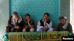 Para pelayat duduk di samping peti jenazah wartawan Afghanistan, Zabihullah Tamanna sebelum upacara pemakaman di Kabul, Afghanistan, 7 Juni 2016.