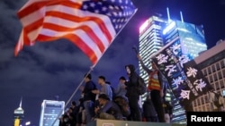 Protestors stand next to a U.S. flag as they attend a gathering at the Edinburgh place in Hong Kong, China, November 28, 2019.