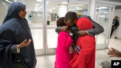 FILE - Ismail Issack, father of Miski Shalle, 11, and Muzamil Shalle, 14, embraces his children as their mother Halima Mohamed, far left, looks on as they reunite for the first time in seven years at John F. Kennedy International Airport in New York.