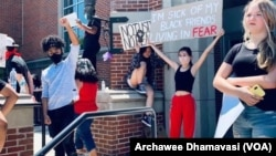 Natasha Dhamavasi (second from right), Archawee Dhamavasi's daughter, holds a banner during a Black Lives Matter protest in Downers Grove village, Illinois on June 7, 2020