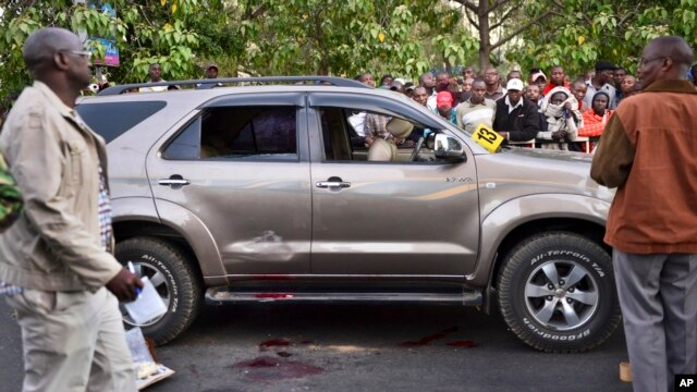 Onlookers gather at the scene after Kenyan lawmaker George Muchai, his two bodyguards and driver were shot dead on a main street in Nairobi, Kenya, Feb. 7, 2015.