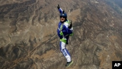 In this Monday, July 25, 2016 photo, skydiver Luke Aikins smiles as he jumps from a helicopter during his training in Simi Valley, Calif.