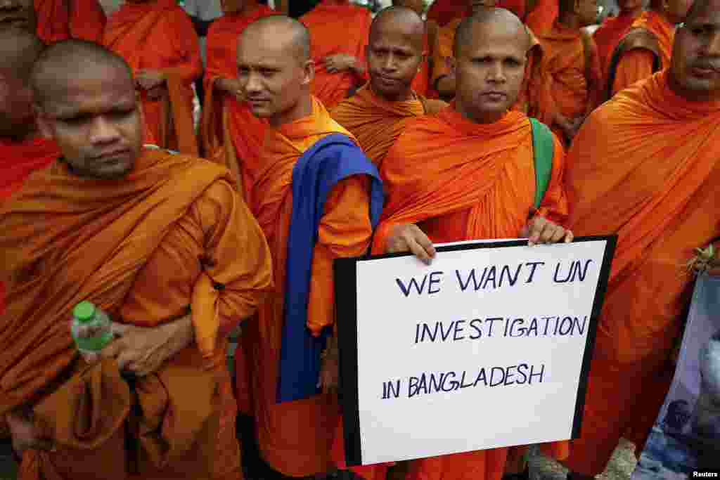 Buddhist monks hold a placard as they protest in front of the U.N. office in Bangkok, Thailand, October 3, 2012.