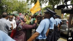 Supporters of former Maldives President Mohammed Nasheed gesture to police officers after the commission of national inquiry released its report in Male, Maldives, August 30, 2012.