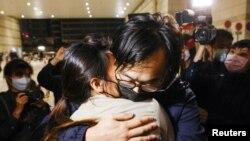 """因為參與""""35+立法會初選""""而被控的其中一名參選人林景楠在週五傍晚獲得保釋後離開法院與妻子擁抱(路透社照片)"""