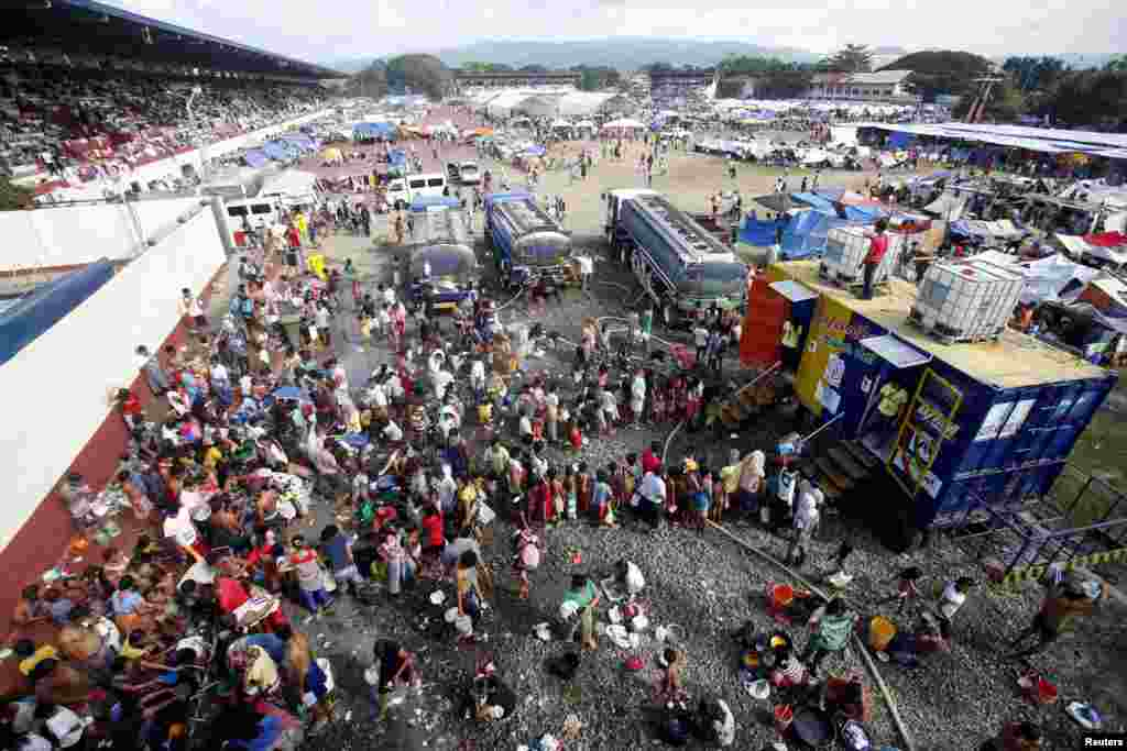 Residents line up for a shower in a stadium turned into an evacuation center in Zamboanga, Philippines, Sept. 18, 2013.