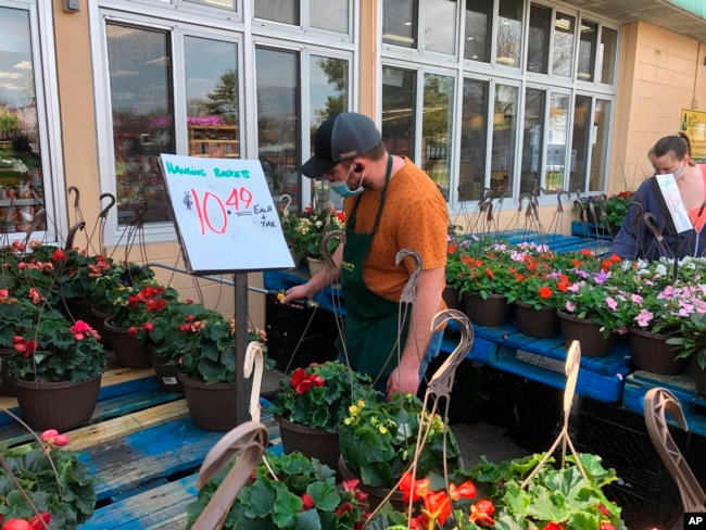 A worker wearing a mask to protect against the coronavirus waters plants at a Joe Randazzo's store in Roseville, Mich., Saturday, May 2, 2020.
