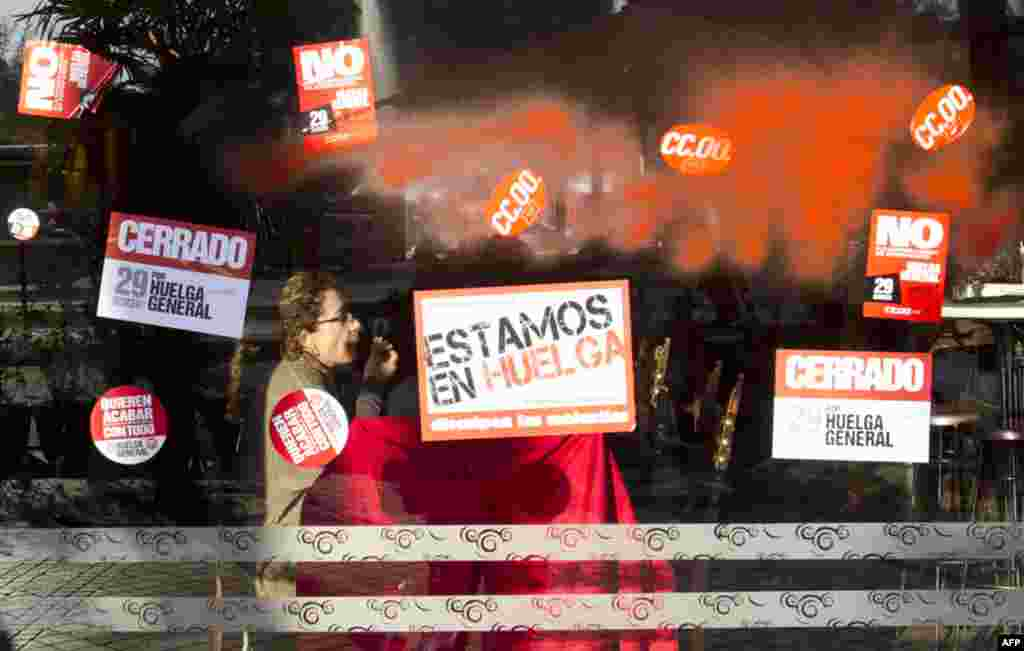 A window covered with red paint and strike stickers reading 'We are on Strike' and 'Closed for the General Strike' in Madrid, March 29, 2012. (AP)
